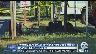 Woman arrested after police cars torched