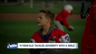 Young boy tackles adversity with a smile